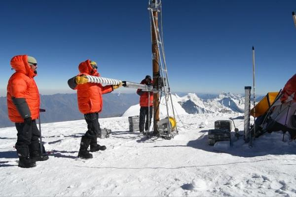 A researcher in an orange coat holds a freshly drilled ice core.